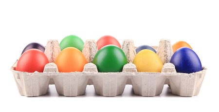 Cardboard egg box with Easter colored eggs. Isolated on a white background photo