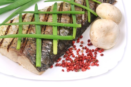 Grilled carp fillet on plate with onion. Whole background. photo