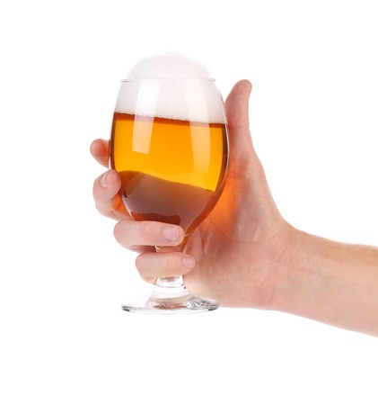 Hand holds glass of beer. Isolated on a white. photo