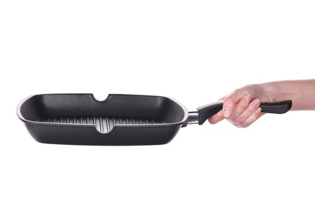 Hand holds a black frying grill pan. Isolated on a white background photo