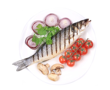 Grilled fish with vegetables. Isolated on a white plate. photo