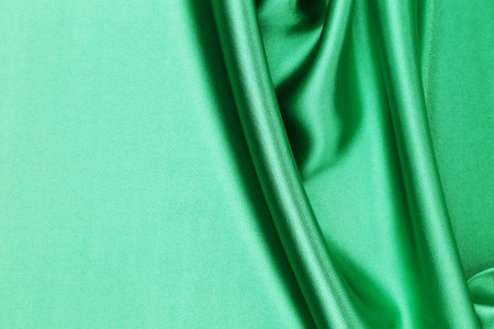 Green silk background with some soft folds and highlights photo