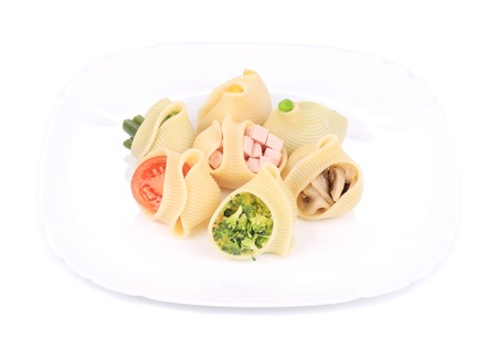 pasta shells stuffed with vegetables and sausage on a white plate. photo