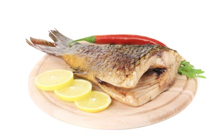 Fried fish tail on wooden table. Isolated on a white background Imagens