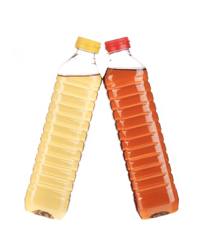 close up of bottles with apple and grape vinegar. isolated on a white background photo
