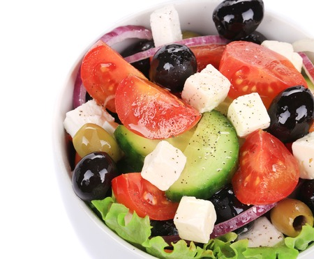 Greek salad in plate. Isolated on a white background. photo