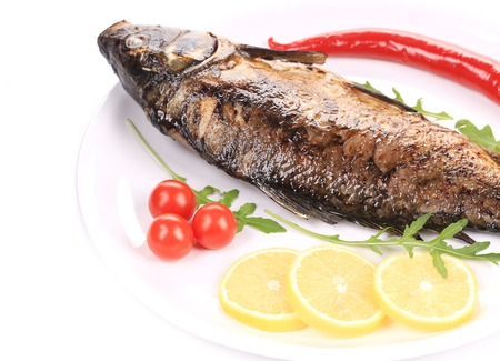 Fried carp with lemon and rukkola. Isolated on a white background. photo