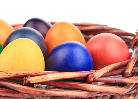 Colorful easter eggs in basket. Isolated on a white background. photo