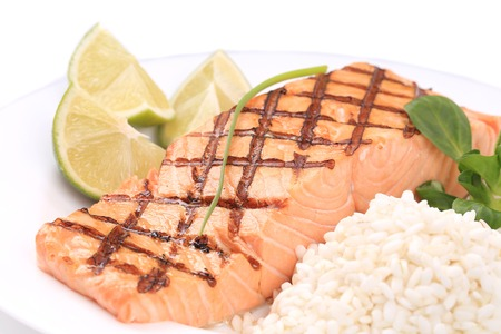 Grilled salmon steak with rice and lime. Isolated on a white background. photo