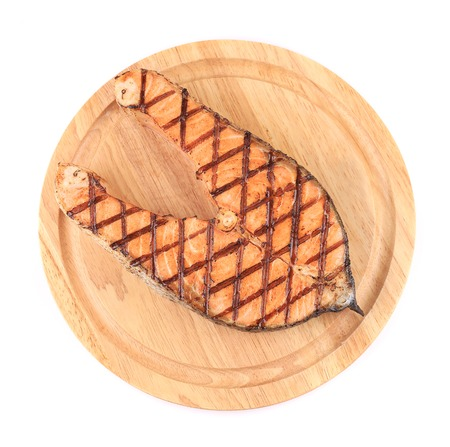 Grilled salmon steak on platter. Isolated on a white background. photo