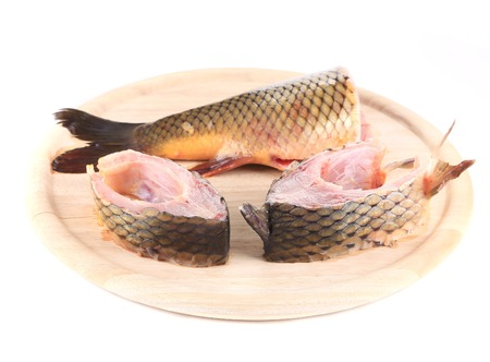 cutting bord: Fillets and tail raw carp on a wooden board. Isolated.