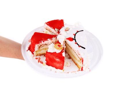 to cake layer: Mano che tiene rosso torta a strati. Isolato su uno sfondo bianco. Archivio Fotografico