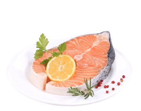 Raw salmon steak with lemon. Isolated on a white background. photo