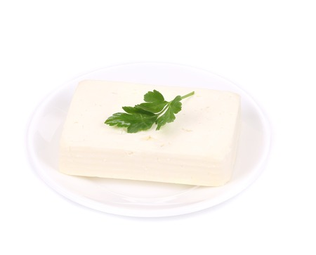 Tofu cheese on white plate. Isolated on a white background. photo