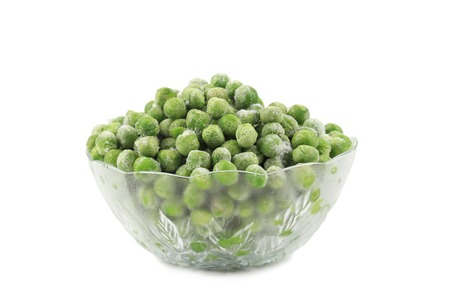Green frozen peas in a glass dish. Isolated on a white background. photo