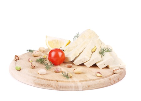 Slices of tofu on wooden platter. Isolated on a white background. photo