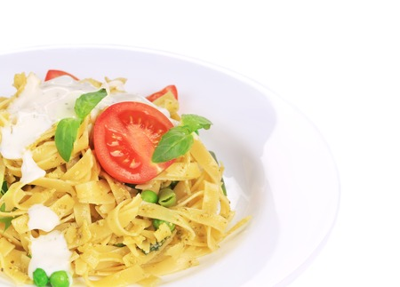 Pasta tagliatelle with pesto sauce and basil. Isolated on a white background. photo
