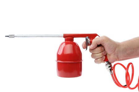 dampen: Hand holds spray gun with plastic spring. Isolated on a white background. Stock Photo