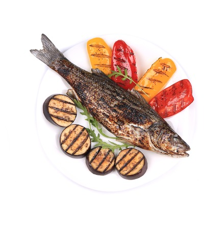 Grilled seabass with vegetables on plate. Isolated on a white background. photo