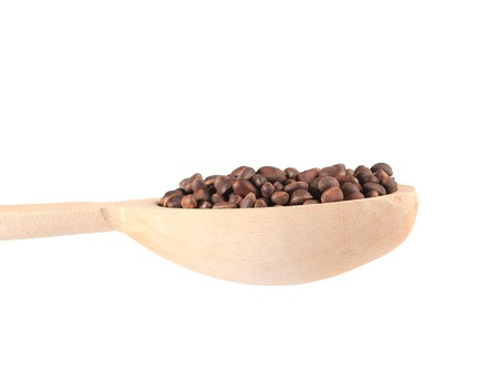 Wooden spoon full with pine nuts. Isolated on a white background. photo