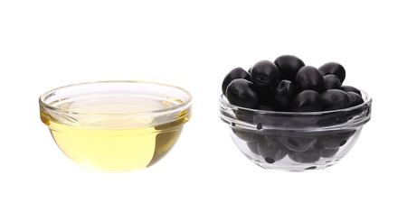 Sunflower oil and olives in glass bowl. Isolated on a white background. photo