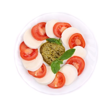 Salad with Tomatoes and Mozzarella Cheese. Isolated on a white background. photo