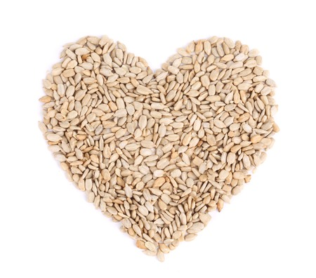Heart shape of pelled sunflower seeds. Isolated on a white background. photo