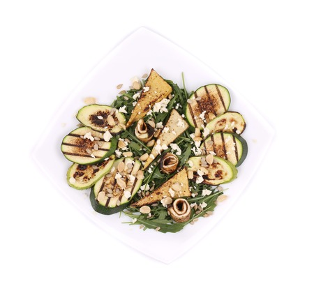 Salad with grilled vegetables and tofu. Isolated on a white background. photo