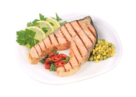 Grilled salmon filler with vegetables. Isolated on a white background. photo