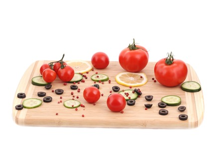 Vegetables and olives on cutting board. Isolated on a white background. photo