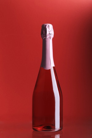 Bottle of pink champagne. Whole pink background. photo
