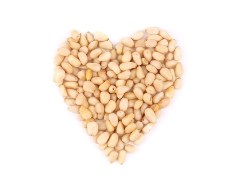 Heart shape from pine nuts. Isolated on a white background. photo