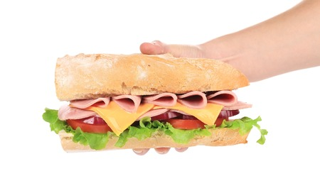 Big fresh sandwich in hand. Isolated on a white background. photo