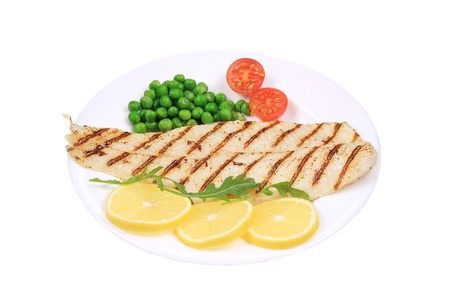 Fish fillet with vegetables. Isolated on a white background. photo