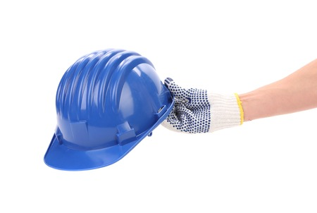 Hand holding blue helmet. Isolated on a white background. photo