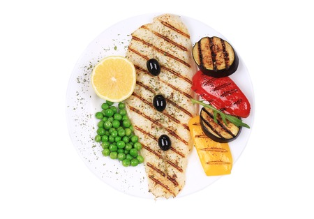 Grilled fish fillet with vegetables. Isolated on a white background. photo