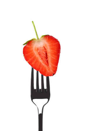 Fresh big strawberry on a fork. Isolated on a white background. photo