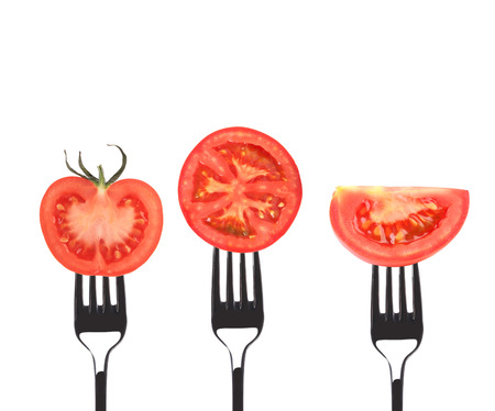 Tomato slices on forks. Isolated on a white background. photo