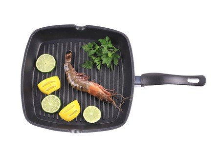 Frying pan with shrimp and lemon slices. Isolated on a white background. photo