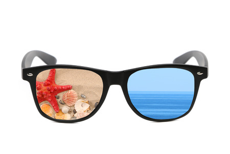 Sunglasses with beach and sea reflection. Isolated on a white background. photo