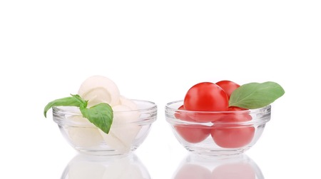 Mozzarella and tomatoes in glass bowl. Isolated on a white background. photo