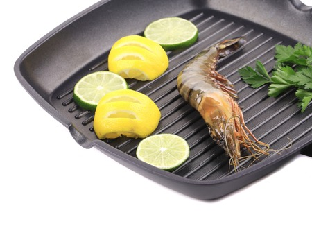 griddle: Frying pan with shrimp and lemon slices. Isolated on a white background.
