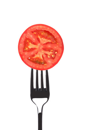 Red juicy tomato on fork. Isolated on a white background. photo