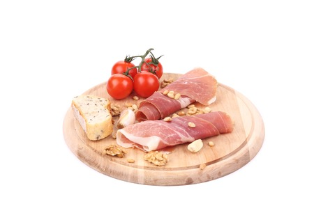 Prosciutto with tomatoes on wooden platter. Isolated on a white background. photo