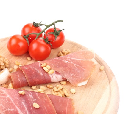Prosciutto with tomatoes on wooden platter. photo