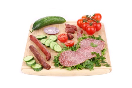Sausage salami and vegetables on wooden platter.  photo