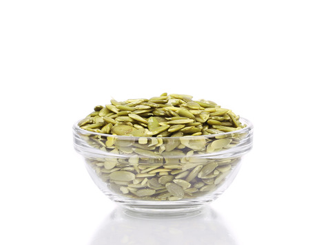 Glass bowl full with pumpkin seeds.  photo