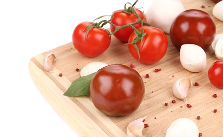 Tomatoes and fresh mozzarella on cutting board. Isolated on a white background. photo