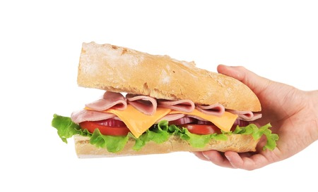 Hand holds french baguette sandwich.  photo