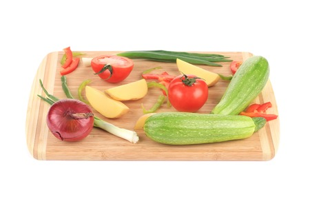 Fresh vegetables on cutting board. Isolated on a white background. photo